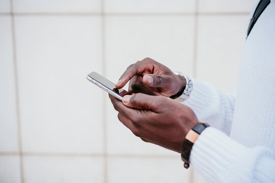 Young businessman using smart phone by wall