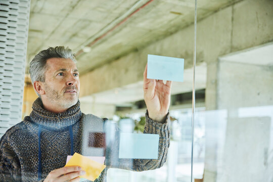 Male businessman putting sticky note while standing by glass wall at office