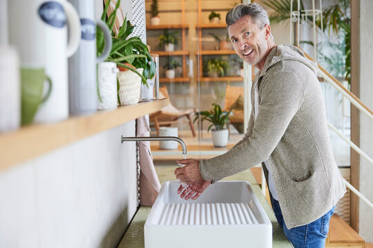 Smiling mature man washing hands while standing by sink at home