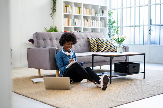 Smiling woman writing in book while sitting by laptop on floor at home