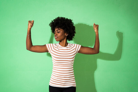 Young woman with eyes closed showing fist while standing against green background