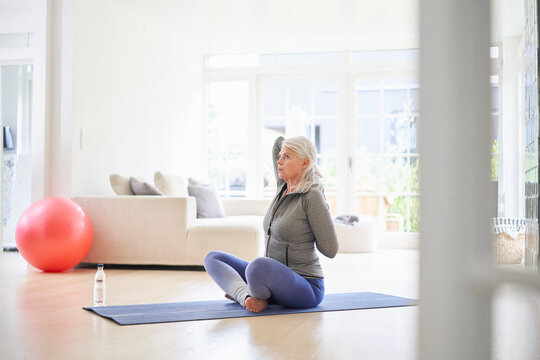 Senior woman exercising with hands behind back in living room