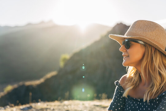 Smiling woman in sunglasses looking away on sunny day during vacations