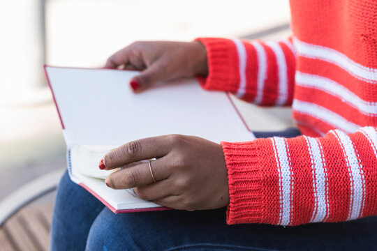 Young woman reading last page of book