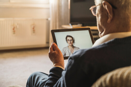 Senior male patient taking advice from female general practitioner on video call through digital tablet