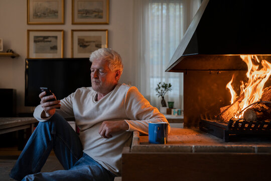 Senior man using mobile phone while sitting by fireplace at home