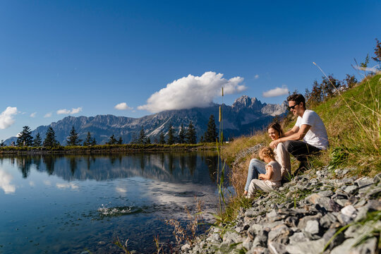 Family with little daughter sitting together on shore of alpine lake