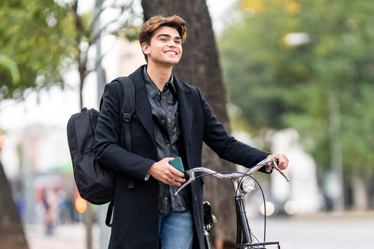 Smiling handsome young man wheeling bicycle in city