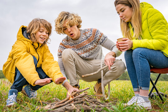 Three siblings starting campfire in grassy field