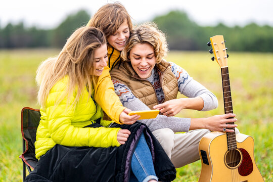 Three siblings using smart phone outdoors during hike