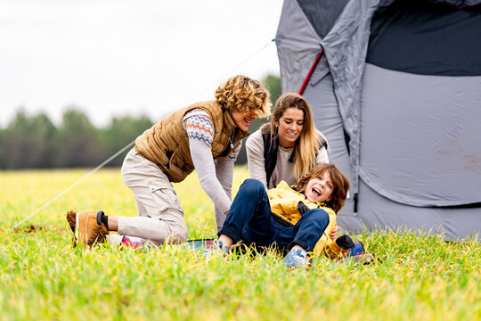 Three siblings playing on grass in front of pitched tent