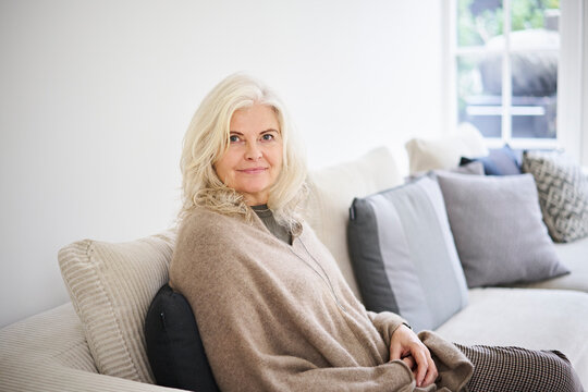 Beautiful senior woman with long white hair sitting on sofa in living room at home