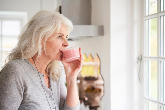 Retired senior woman drinking strawberry smoothie in kitchen at home