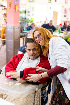 Smiling female caregiver with disabled man in nursing home