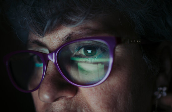 Close-up of senior woman wearing eyeglasses working at home