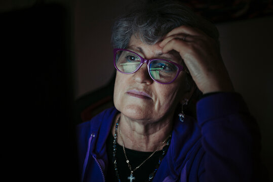 Close-up of senior teacher with head in hand working over laptop at home