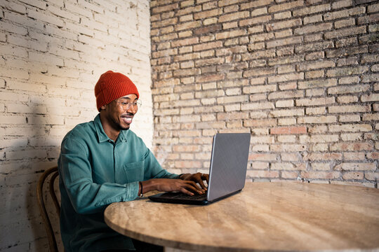 Smiling male entrepreneur working on laptop while sitting on chair at table
