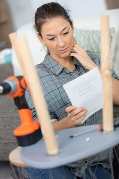 woman reading instructions for assembling furniture