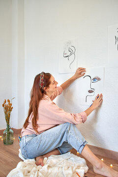 Smiling female artist pasting drawing art on wall in living room