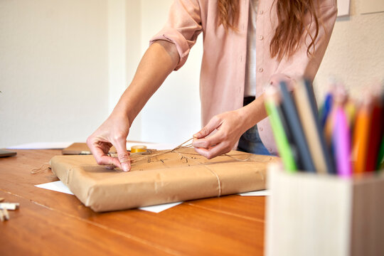 Female freelancer preparing delivering package by tying knot from string in living room
