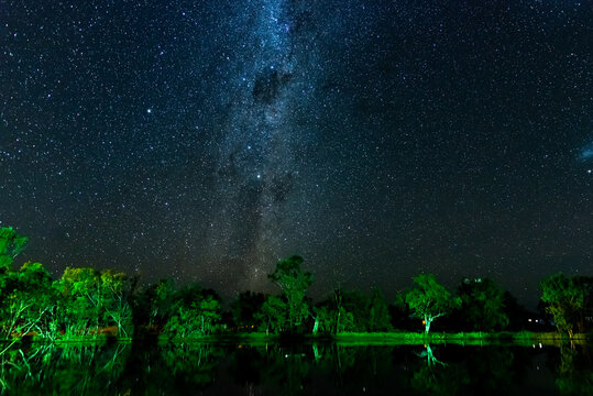 Starry night sky with Milky Way and reflections of trees in a lagoon