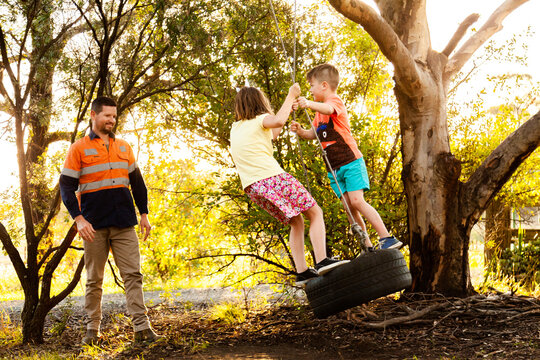 Dad playing with children in backyard on tyre swing in the afternoon