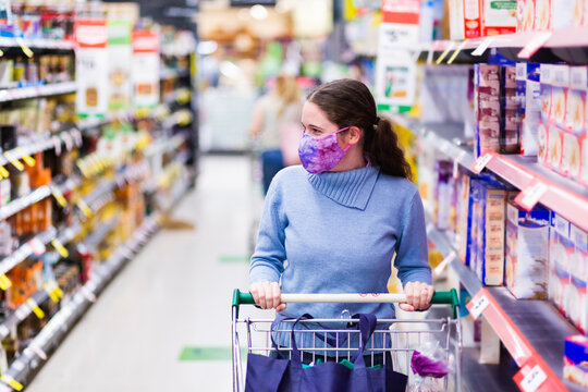Young woman in her twenties wearing a face mask in shopping aisle, choosing what to buy