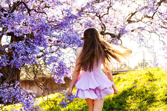 Happy teen girl with long hair and purple dress spinning and twirling beside flowering jacaranda
