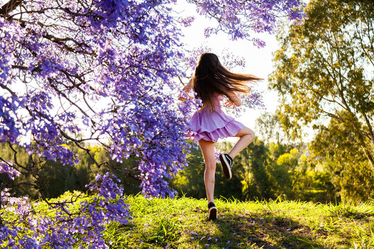 Dancer spinning on hillside beside a purple jacaranda tree