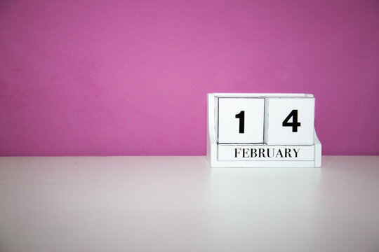 Closeup of a small wooden cube calendar on 14 February against a pink background
