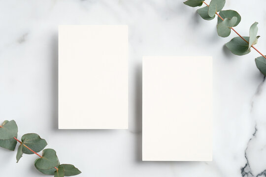 Wedding invitation cards design. Flat lay blank paper card mockup and eucalyptus leaves on marble background