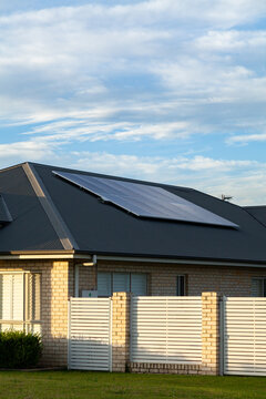 last daylight on front of house with solar panels installed on roof of home