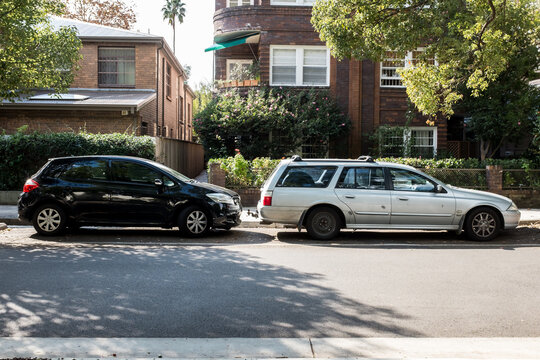 old and new car parked in a suburban street
