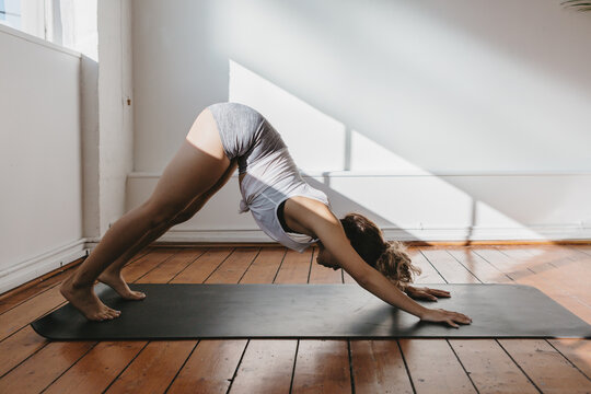 Girl in the downward dog yoga pose in a gym