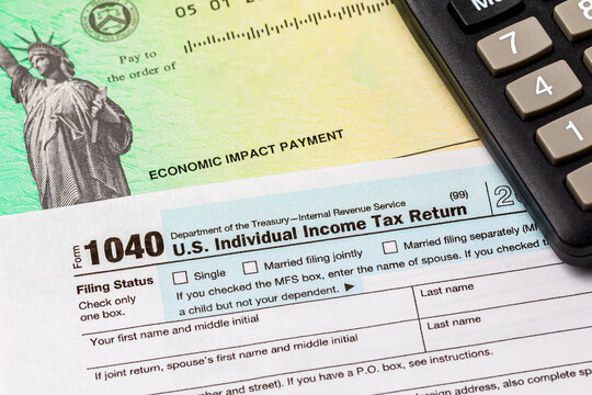 1040 individual income tax return form and economic impact payment or stimulus check. Concept of filing taxes, taxable income and tax information