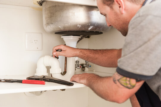 Plumber installing a sink and pipes