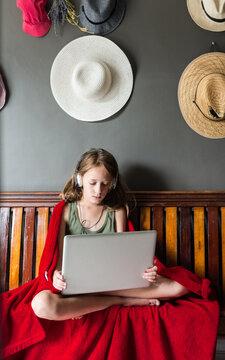 tween girl using a laptop, with headphones