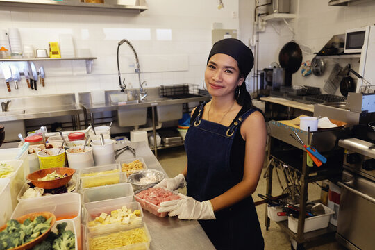 Multicultural Asian chef cooking in Thai small business restaurant
