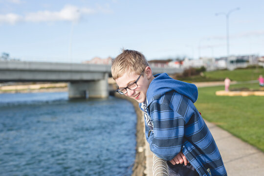 Boy leaning over fence near river