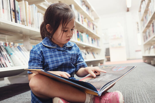 Young student girl reading in library