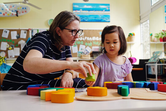 Multicultural teacher and child playing wooden blocks puzzles in kindergarten