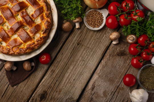 Pie with meat and mushrooms with ingredients for cooking tomatoes, mushrooms, parsley on a wooden background top view