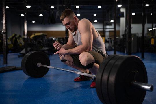 Sportsman sitting near barbell in gym