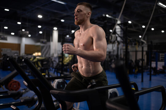 Sweaty male athlete running on treadmill