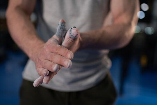 Cropped athlete spreading magnesium on hands