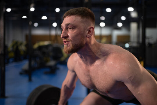 Muscular athlete doing snatch exercise during workout
