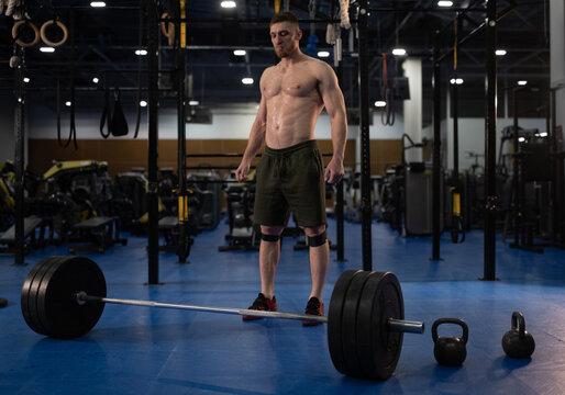 Sweaty sportsman standing near barbell