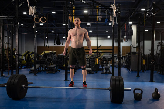 Strong athlete preparing to lift barbell