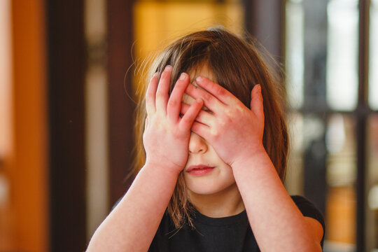 Close-up of a small child hiding behind her hands