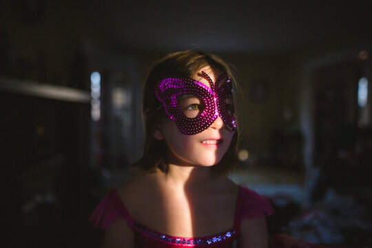 close-up of small child lit up in dark room wearing butterfly costume